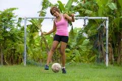 La mujer asiática feliz y emocionada joven en deporte viste jugar al fútbol que se divierte en el campo de fútbol de la selva con Foto de archivo