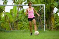 La mujer asiática feliz y emocionada joven en deporte viste jugar al fútbol que se divierte en el campo de fútbol de la selva con Fotos de archivo libres de regalías