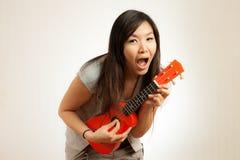 La mujer asiática goza del ukelele Imagenes de archivo