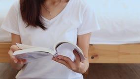 La mujer asiática hermosa del primer relaja el libro de lectura que se sienta en dormitorio en casa almacen de metraje de vídeo