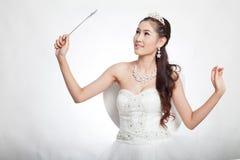 La mujer asiática hermosa del retrato en el vestido de boda blanco con el cetro de hadas con ángel se va volando Imagen de archivo