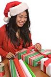 La mujer asiática hermosa envuelve regalos de Navidad Imagenes de archivo