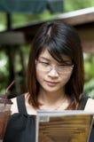 La mujer asiática hermosa goza de té helado. Fotografía de archivo libre de regalías