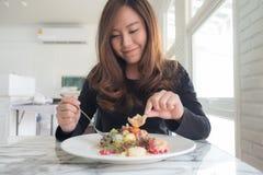 La mujer asiática hermosa goza el comer de la ensalada de frutas en la tabla en restaurante foto de archivo libre de regalías
