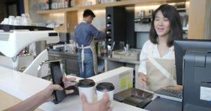 La mujer asiática hermosa hace el café para llevar para un cliente que pague por el teléfono móvil sin contacto al sistema de la  metrajes