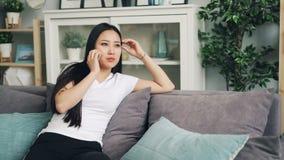 La mujer asiática hermosa joven está llamando al amigo en el teléfono móvil que habla y que sonríe en sala de estar en casa Dispo metrajes