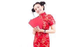 La mujer asiática hermosa lleva el cheongsam en el fondo blanco Celebrar sobres rojos y sonrisa en Año Nuevo chino Foto de archivo