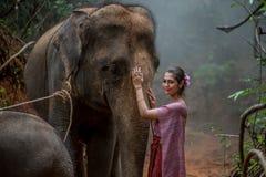La mujer asiática hermosa lleva el vestido tailandés con su elefante, elepha Fotos de archivo libres de regalías