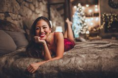 La mujer asiática hermosa se está sentando en cama en casa cerca del árbol de navidad en interior acogedor Interior con la Navida imagenes de archivo