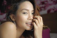 La mujer asiática hermosa y dulce joven con los pendientes y compone la sonrisa feliz y alegre mirando la cámara imagen de archivo