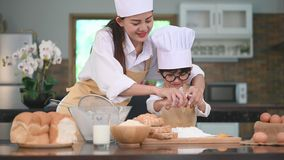 La mujer asiática hermosa y el niño pequeño lindo con las lentes se preparan a cocinar en cocina en casa junto Formas de vida y f almacen de metraje de vídeo
