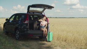 La mujer asiática impaciente espera al amigo para el viaje del coche almacen de metraje de vídeo