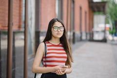La mujer asiática joven con los vidrios sostiene smartphone en manos Imagen de archivo