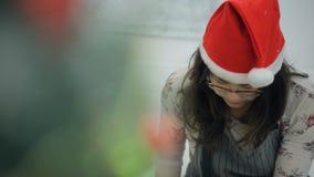 La mujer asiática joven con los vidrios y el casquillo de Papá Noel preparan decoraciones almacen de metraje de vídeo
