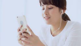 La mujer asiática joven del retrato hermoso que sienta música que escucha del auricular feliz con se relaja y goza en el dormitor