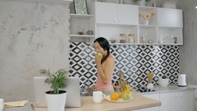 La mujer asiática joven está comiendo la manzana que se coloca en cocina en el apartamento almacen de video