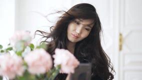 La mujer asiática joven está tomando un selfie en el viento en casa metrajes