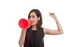La mujer asiática joven hermosa anuncia con el megáfono imagenes de archivo