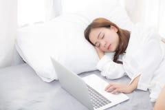 La mujer asiática joven hermosa con el ordenador portátil que se acostaba en el dormitorio, muchacha cansó sueño con el cuaderno  Fotografía de archivo libre de regalías