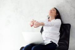 La mujer asiática joven hermosa con estiramiento del ordenador portátil y el ejercicio se relajan después de éxito del trabajo imagen de archivo libre de regalías