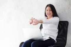 La mujer asiática joven hermosa con estiramiento del ordenador portátil y el ejercicio se relajan después de éxito del trabajo imagen de archivo