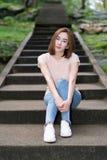 La mujer asiática joven hermosa en casual con mezclilla, sonríe y se sienta en la escalera en el parque nacional, Tailandia foto de archivo
