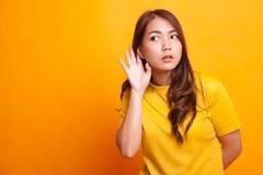 La mujer asiática joven hermosa escucha algo fotos de archivo libres de regalías