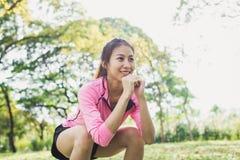 La mujer asiática joven las posiciones en cuclillas para el ejercicio aumenta su cuerpo de la belleza en parque rodea con los árb Imágenes de archivo libres de regalías