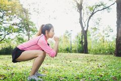 La mujer asiática joven las posiciones en cuclillas para el ejercicio aumenta su cuerpo de la belleza en parque rodea con los árb Fotos de archivo libres de regalías