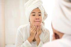 La mujer asiática joven que presiona su cara, intentando quita acné fotos de archivo