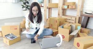 La mujer asiática joven que trabaja en casa, negocio joven comienza para arriba con negocio en línea almacen de video