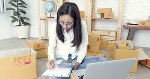 La mujer asiática joven que trabaja en casa, negocio joven comienza para arriba con negocio en línea almacen de metraje de vídeo