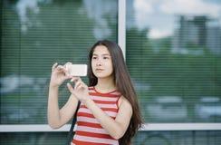 La mujer asiática joven que usa smartphone y toma una imagen Imagen de archivo