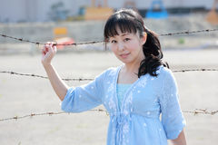 La mujer asiática joven se coloca en una cerca del barbwire Fotografía de archivo