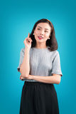 La mujer asiática preciosa sonriente se vistió en vestido del estilo del perno-para arriba sobre el bl Foto de archivo