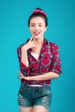 La mujer asiática preciosa sonriente se vistió en vestido del estilo del perno-para arriba sobre el bl Imágenes de archivo libres de regalías