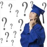 La mujer asiática profundamente en vestido de la graduación del pensamiento que llevaba aisló whi Foto de archivo