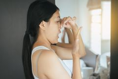 La mujer asiática que cubre su boca y huele su respiración con las manos que el upter despierta, mún olor foto de archivo