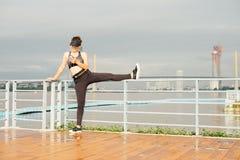 La mujer asiática que hace estirar ejercita al aire libre a lo largo de sidew de la ciudad Foto de archivo libre de regalías