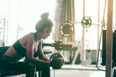 La mujer asiática que se sienta en el club del gimnasio y escucha música con la relajación de a Imagen de archivo libre de regalías