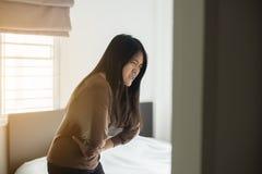 La mujer asiática que tiene dolor de estómago doloroso en dormitorio después de despierta, calambre femenino del período Fotos de archivo