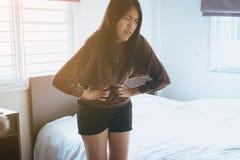 La mujer asiática que tiene dolor de estómago doloroso en dormitorio después de despierta, sufrimiento femenino de los calambres  Fotografía de archivo