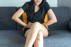 La mujer asiática que tiene dolor de estómago doloroso en dormitorio después de despierta, sufrimiento femenino de los calambres  Fotos de archivo