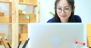 La mujer asiática que trabaja en casa, negocio joven comienza para arriba con negocio en línea o concepto de la PME almacen de video