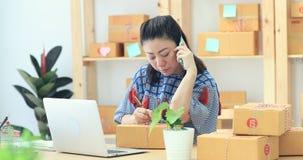 La mujer asiática que trabaja en casa, negocio joven comienza para arriba con negocio en línea o concepto de la PME metrajes
