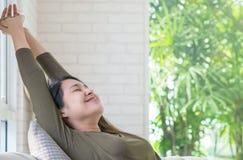 La mujer asiática se relaja en el sofá en su tiempo libre en fondo del sitio Fotografía de archivo