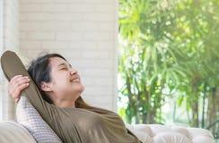 La mujer asiática se relaja en el sofá en su tiempo libre en fondo del sitio Fotos de archivo