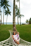 La mujer asiática se relaja en la playa Imagen de archivo libre de regalías