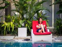 La mujer asiática se relaja en lado de la piscina Fotografía de archivo libre de regalías