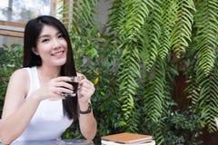 La mujer asiática se sienta en el café al aire libre adulto femenino joven con natural Imágenes de archivo libres de regalías